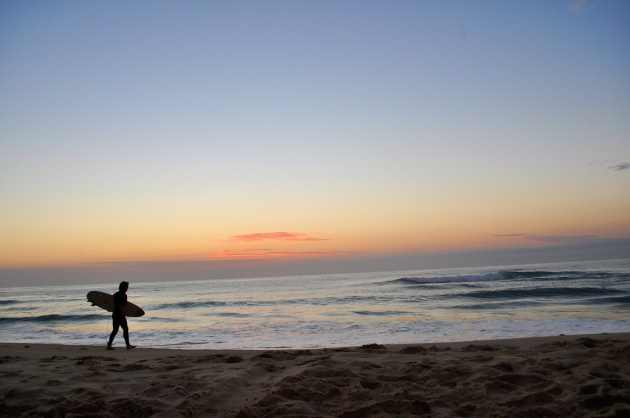 A surfer heading out before sunrise