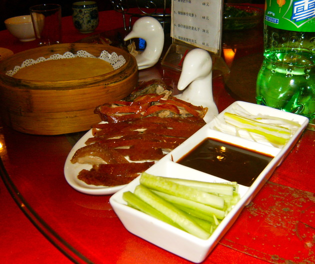 The duck meat is served on the plate with the duck head. Cute, huh?