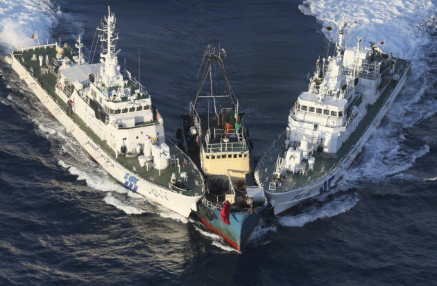 A boat, center, is surrounded by Japan Cost Guard's patrol boats after some activists descended from the boat on Uotsuri Island, one of the islands of Senkaku in Japanese and Diaoyu in Chinese, Wednesday, Aug. 15, 2012. (AP Photo/Yomiuri Shimbun, Masataka Morita)