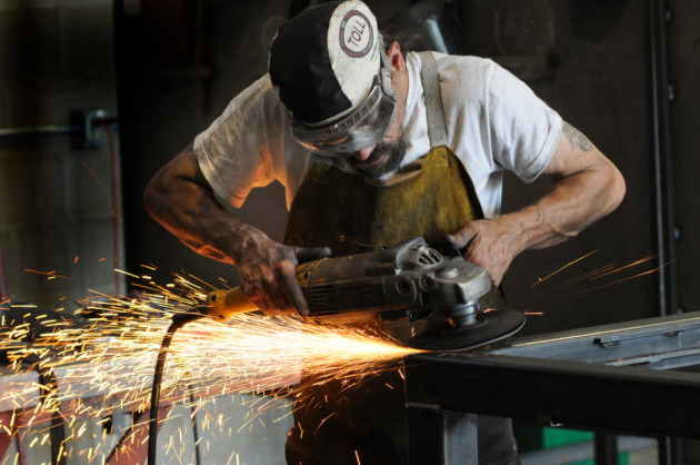 Mark Dauer uses a grinder on a welding project at Code Welding in Blaine, Minn. (Richard Sennott/Star Tribune)