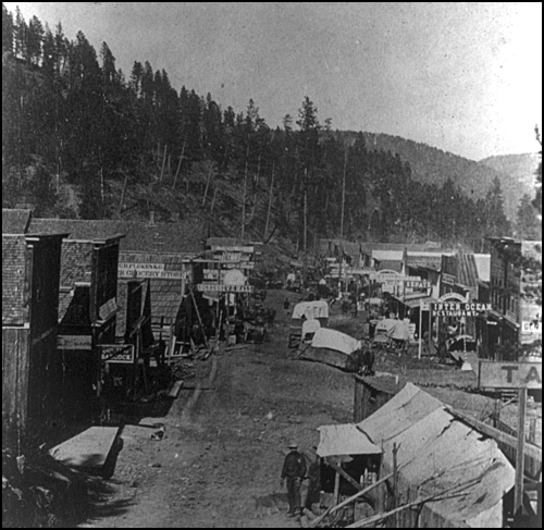 "Deadwood in 1876: ""Its one street runs up and down the gulch, making the same number of twists and turns the gulch does, and narrows and widens with the gulch, so that at some places it is wide enough to be almost respectable while at others it is so narrow that it will barely admit a team and wagon."""