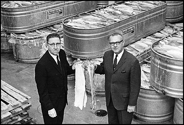 There wasn't much to smile about in a 1950s lutefisk factory. Arthur Boscher, left, and David Arneson of Lyon Food Products hoisted some slimy goodness. (Minneapolis Star photo by Jack Gillis)