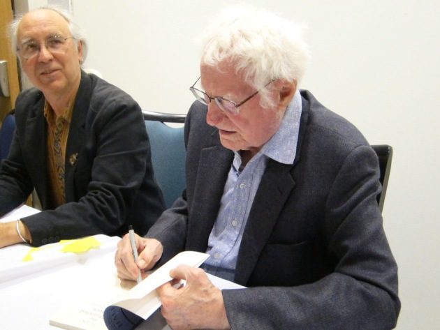 Thomas R. Smith and Robert Bly sign books after Tuesday's reading.