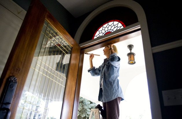 Mary Leer does touch-up work on the front door of a house she recently sold in North Minneapolis.