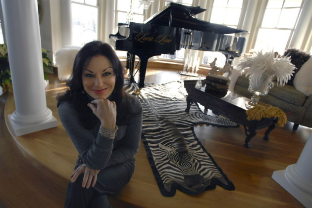 Lorie Line with one of her pianos during a tour of the house several years ago.