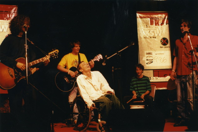 Vic Chesnutt performed at SXSW in 1996 with a few of his local admirers: (from left) Gary Louris, wannabe-Minnesotan Jeff Tweedy, Noah Levy and Kraig Johnson. / Photo by Tim Campbell