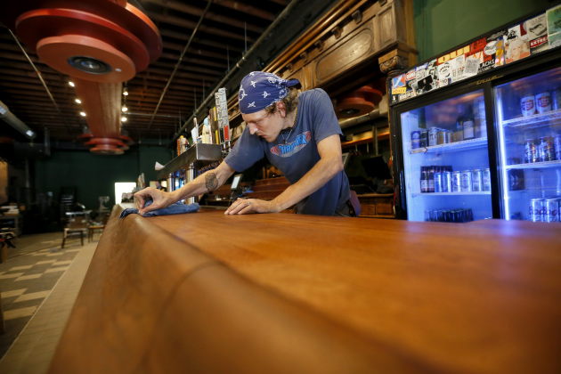 Daniel Hornfeldt wiped down the new bar top. / Jerry Holt, Star Tribune