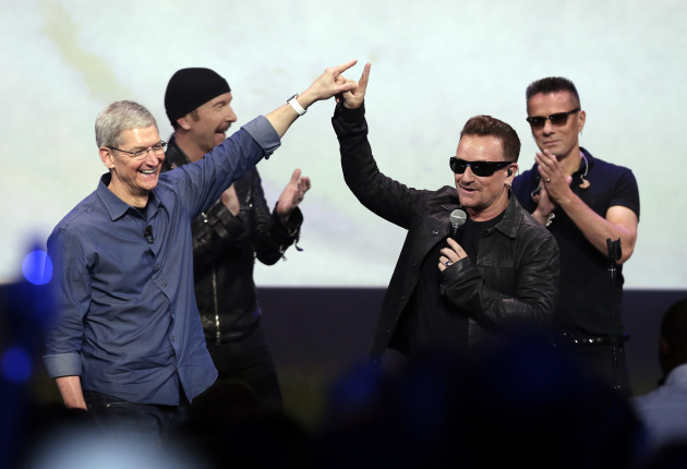Apple CEO Tim Cook, left, thanked U2 for performing at his launch party and probably saving the world in Cupertino, Calif., earlier today. / AP Photo/Marcio Jose Sanchez