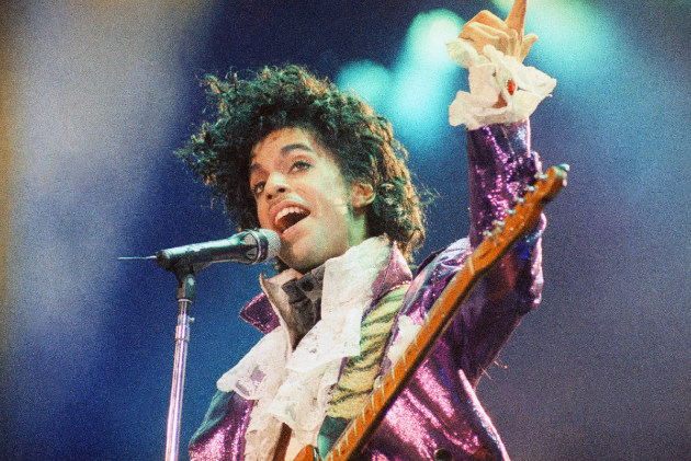Prince playing to the dearly beloved circa 1985. / Associated Press, Liu Heung Shing