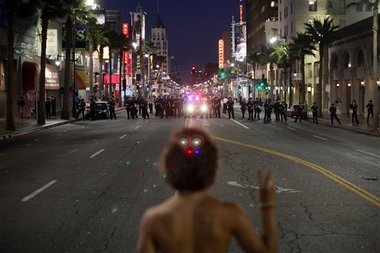 Noel Buller, 21, from Los Angeles, stands in the middle of Hollywood Boulevard in Los Angeles holding up a peace sign while facing a line of Los Angeles Police last Wednesday. (AP Photo/Jay L. Clendenin/Los Angeles Times)
