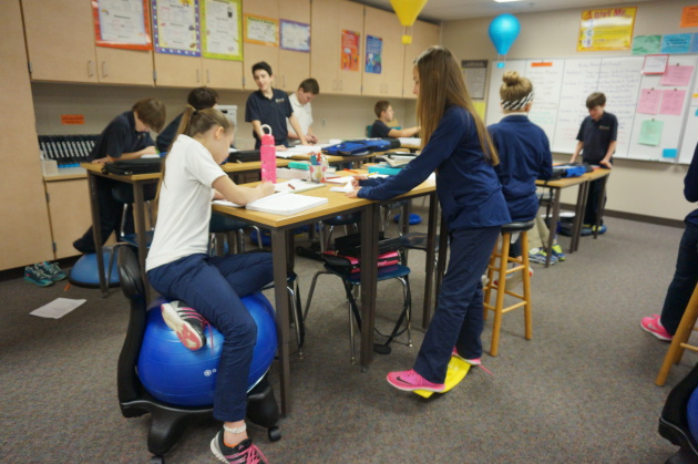Students use standing desks exercise equipment to boost learning