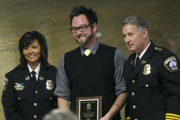 John Sundahl (center) receives an award from outgoing Chief Tim Dolan (right) and his likely successor, Assistant Chief Janée Harteau (photo by Elizabeth Flores)