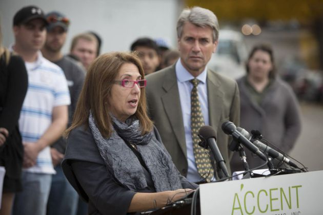 Shereen Rahamim, the wife of Accent Signage owner Reuven Rahamim, spoke Monday of her husband and five others killed in the Sept. 27 shooting as Mayor R.T. Rybak looks on. (Jennifer Simonson, Associated Press)