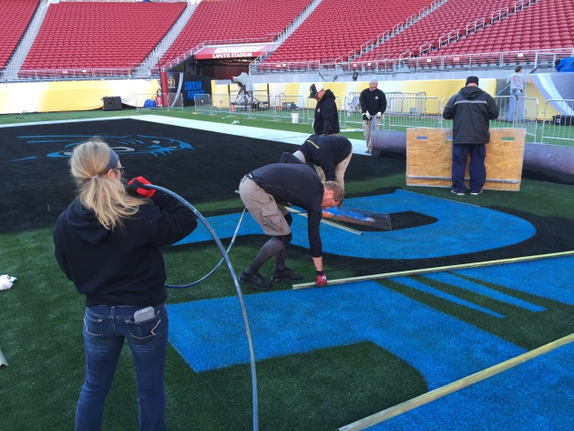 Georgeanna Heitshusen helps paint the Carolina endzone for Super Bowl 50