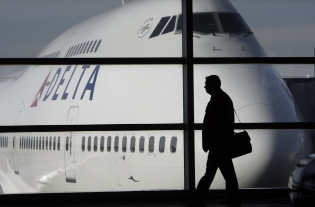 In this Jan. 21, 2010 file photo, a passenger walks past a Delta Airlines 747 aircraft in McNamara Terminal at Detroit Metropolitan Wayne County Airport in Romulus, Mich. (AP Photo/Paul Sancya, file)