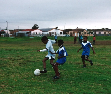 Kids playing soccer in South Africa in shoes donated by Minnesotans.