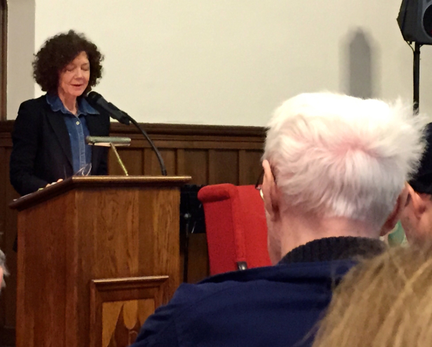 Joyce Sutphen reads; Robert Bly is in the foreground.