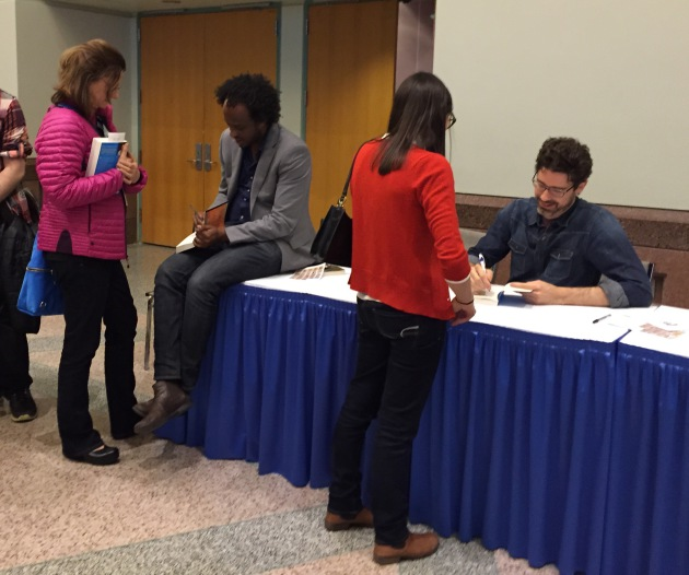 Writers Dinaw Mengestu and Joshua Ferris autograph books after their Saturday night keynote event.