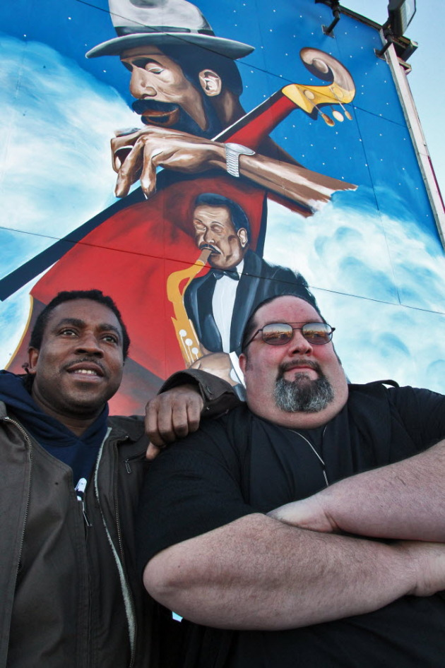 Artist Charles Caldwell and Bar Manager Mike Oker stand in front of the mural Caldwell created on the side of the 4th Street Saloon.