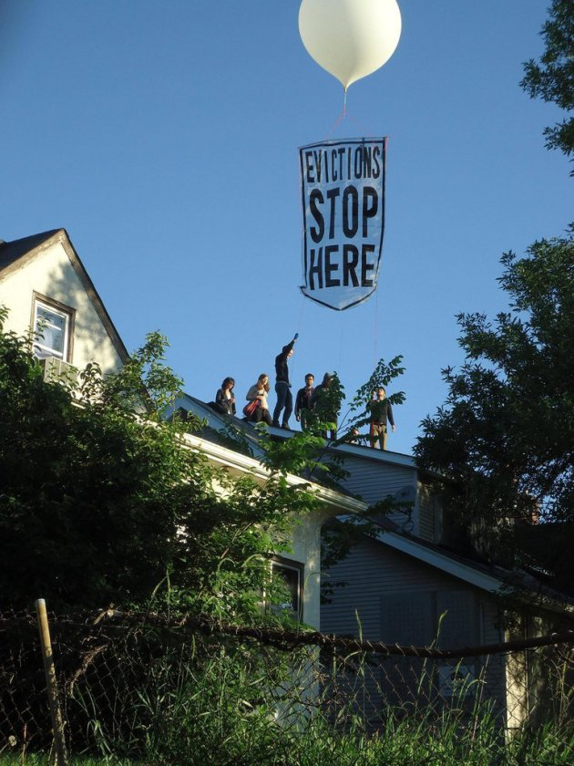 Protesters deploy balloon banner over Cruz house. Photo courtesy of Occupy Homes MN