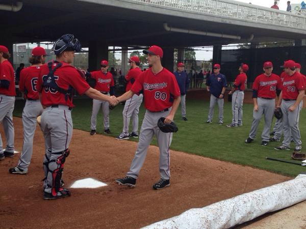 Catcher Stuart Turner shakes hands with pitcher Taylor Rogers during communications exercise in Twins' bullpen on Friday.