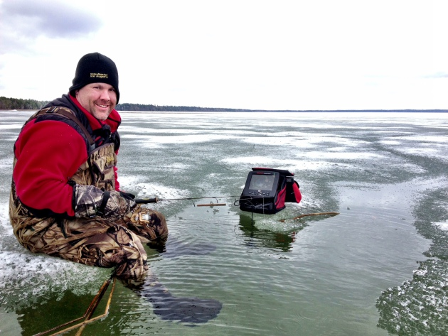 "Bryan ""Beef"" Sathre of Fathead Guide Service hams it up on the ice in shallow water on Pike Bay Lake"